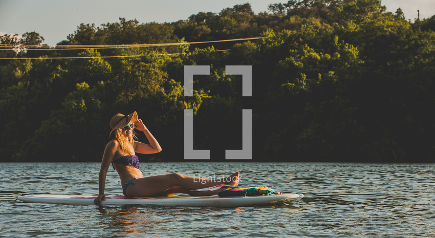 woman lying on a paddle board