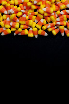 border of candy corn on a black background