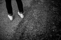 A teen girl's feet standing on asphalt.