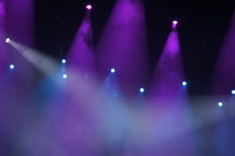 Purple and blue spotlights focused on concert performance stage through theatrical fog or smoke.