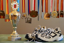 A pair of running shoes next to a trophy and medals.