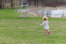 toddler girl running in grass