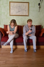 couple sitting on a sofa ignoring each other