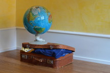 a globe on a packed suitcase