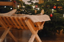 manger in front of a Christmas tree in a house