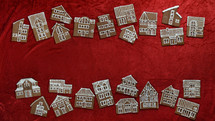 two rows of  self baked different gingerbread house cookies with numbers on them as advent calendar on red