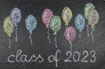chalk on slate with balloons and the words: class of 2023
