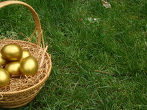 Golden Easter eggs in a basket in the grass.