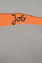 torn open kraft paper over orange paper with the name of the book Job