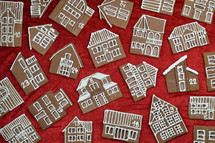 crisscross pattern out of 24 self baked different gingerbread houses on red as edible advent calendar