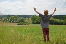 child with raised arms in adoration outdoors at a meadow.