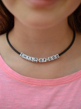 CHILD OF GOD written on pearls at a necklace around a kids neck