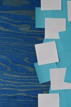 border of blue and white notepads on a blue wooden board