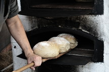 freshly baked bread out of an old timey wood fired oven, 