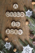 star ornaments, pine cones, snow, pine boughs and the words A CHILD IS BORN on wooden slices