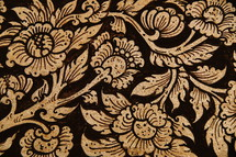 Laotian flower pattern. Gold foil on painted wood. Abstract floral background