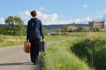 a woman walking carrying luggage on a rural road