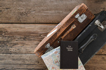 La Sainte Bible on luggage - two old weathered suitcases with a map of Paris and a french bible on a rustic wooden floor