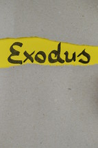 torn open kraft paper over yellow paper with the name of the book Exodus