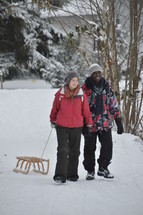 young couple walking hand in hand in the snow and pulling their sled behind