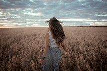 a woman walking through a field of brown grasses