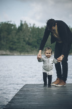 father and toddler child walking on a dock
