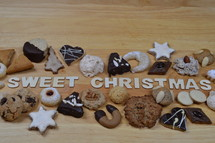 different kinds of Christmas cookies on a breadboard around the words: SWEET CHRISTMAS