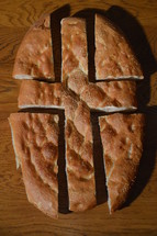 Bread broken into pieces showing the shape of a cross.
