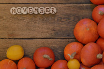 Pumpkins on wooden planks with pieces of wood spelling the word NOVEMBER.