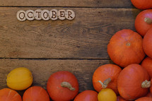 Pumpkins on wooden planks with pieces of wood spelling the word OCTOBER