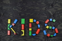 the word KIDS out of colorful wooden toy blocks on black wooden background