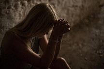 woman sitting with praying hands and head bowed