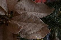 burlap poinsettia ornamenti on a Christmas tree