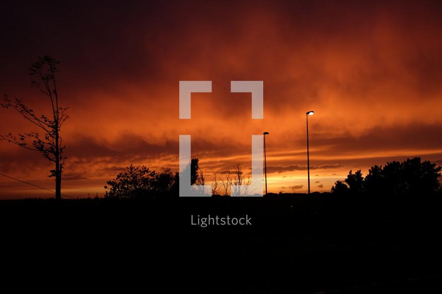 street lights and an orange sky at sunset