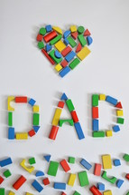 wooden blocks in the shape of a heart and word dad