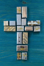 many little presents shaping a cross on teal wooden background