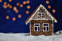 home made gingerbread house with bokeh sky out of blue velvet and christmas lights as advent decoration