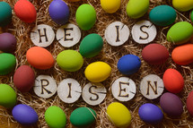 the words: HE HAS RISEN burned in wooden slieces between colorful painted eggs in straw