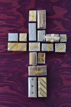 many little presents shaping a cross on purple wooden background