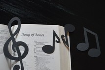 The Bible open to Song of Songs with paper musical notes covering it.