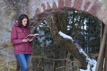 a woman reading a Bible outdoors in winter