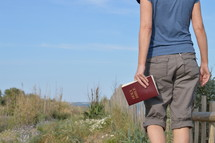 woman walking with Bible in hand in the dunes near the beach