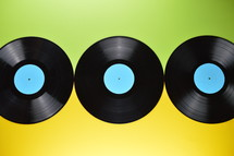 three old black vinyl records with blank cyan labels on yellow and green background