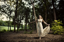 woman in a  lace dress running in a forest