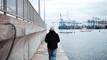 a man walking on a sidewalk at a harbor