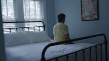 man sitting on a bed praying