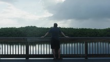 a man standing on a deck looking out at a lake