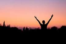 man with his hands raised in praise and worship to God