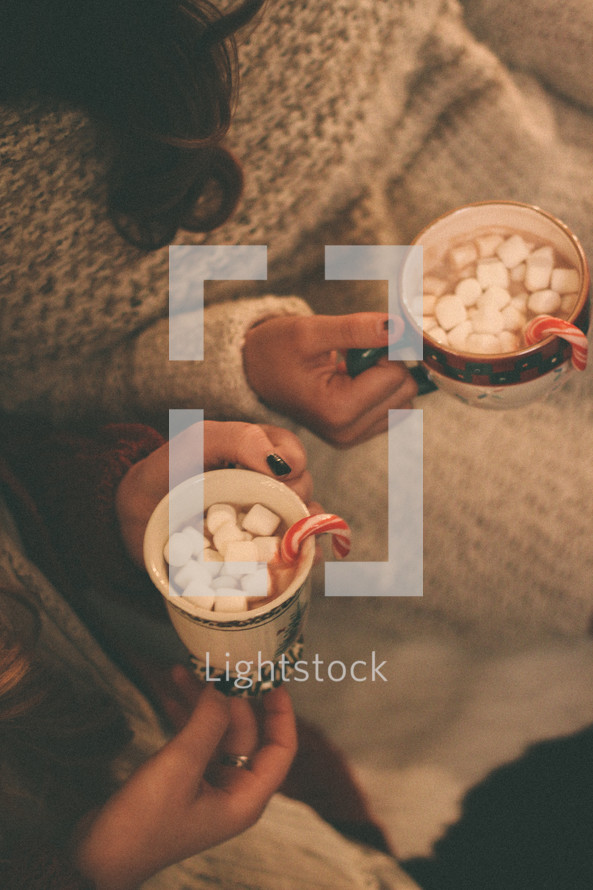 women holding mugs of hot cocoa