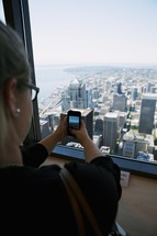 Woman photographing the city skyline with a smart phone from an observation deck.